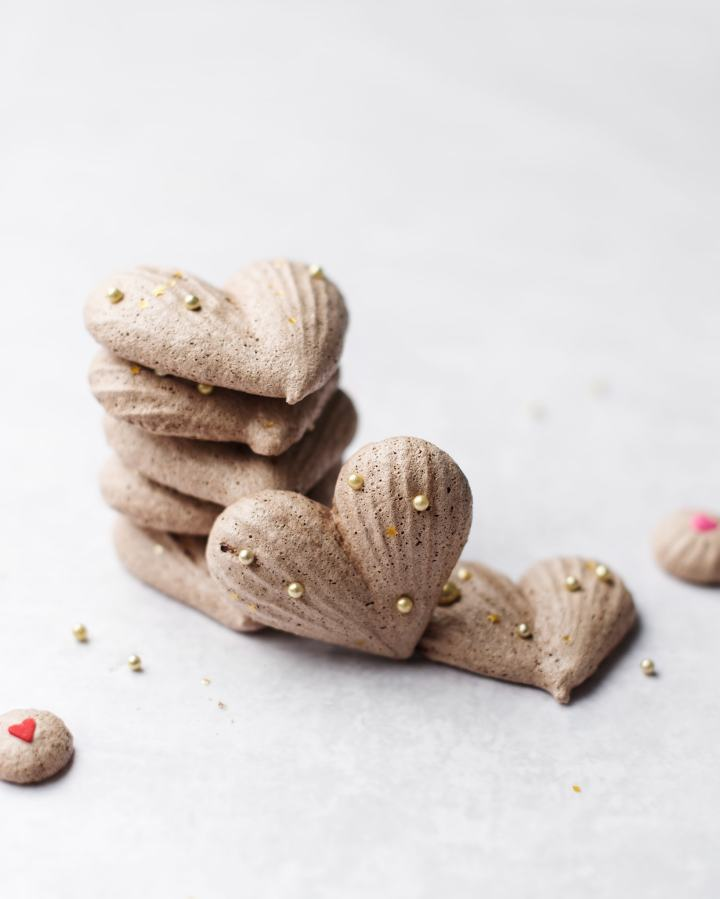 A stack of heart-shaped chocolate meringues with gold sprinkles