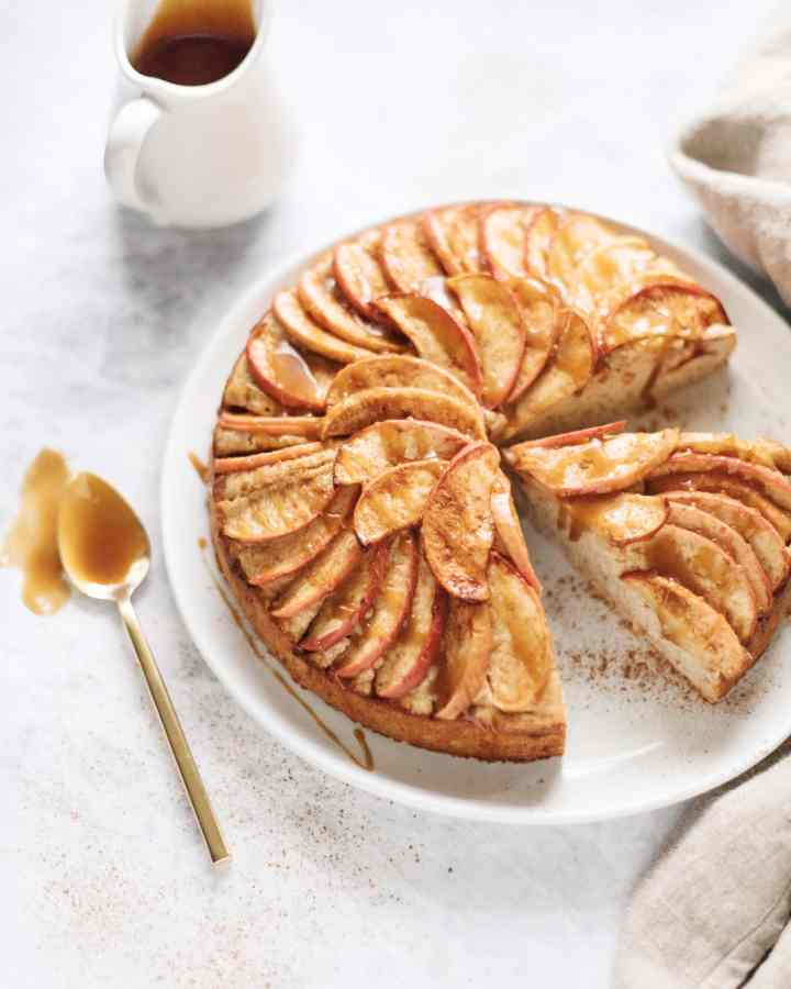 A slice cut out of a spiced apple cake with salted maple caramel drizzle