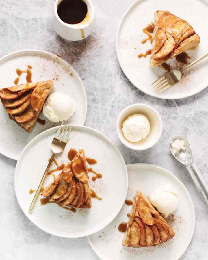 4 slices of spiced apple cake drizzled with salted maple caramel on white plates with scoops of vanilla ice cream