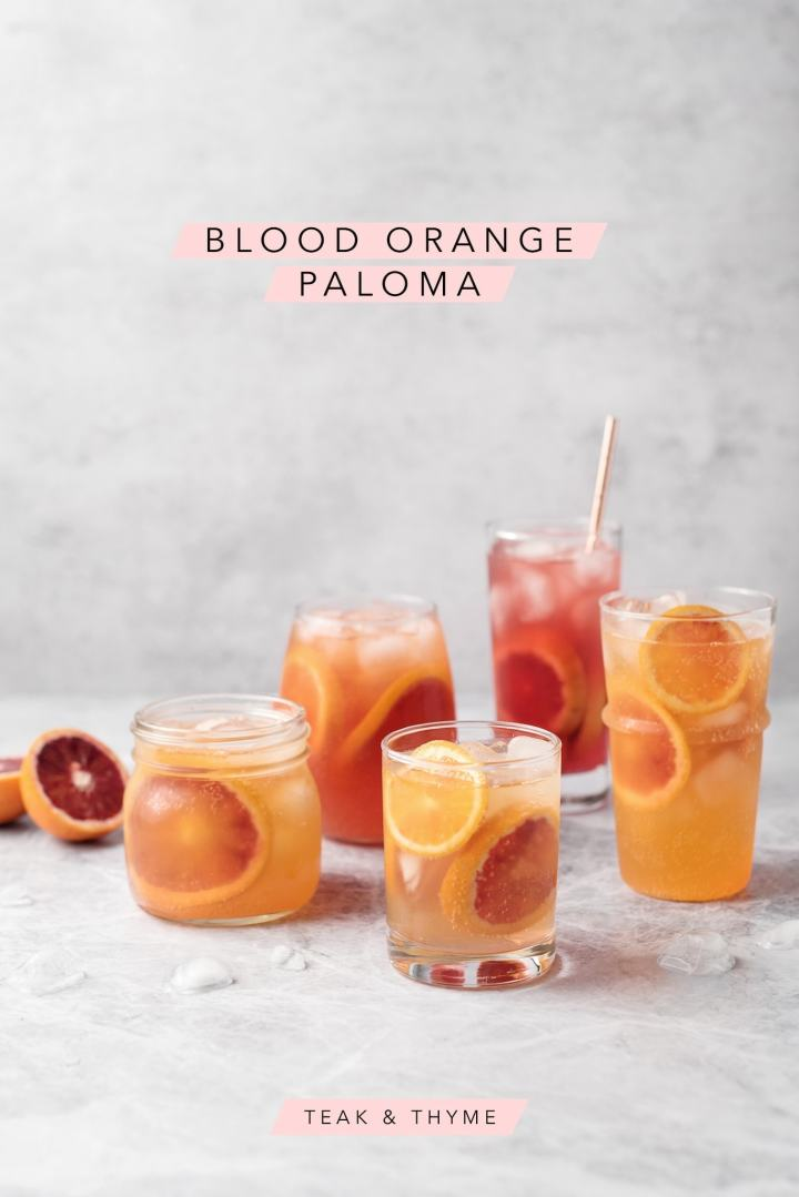 Glasses of blood orange palomas on a grey background with text overlay