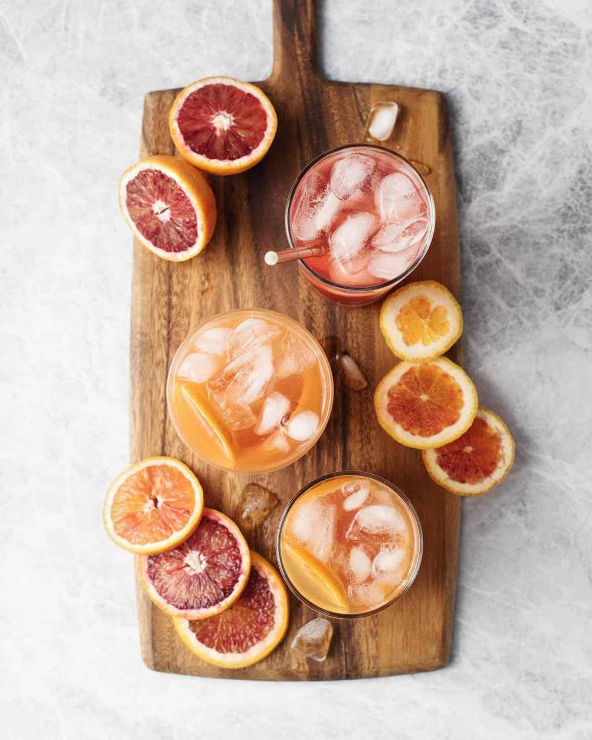 Glasses of blood orange palomas and blood orange slices on a wooden serving board