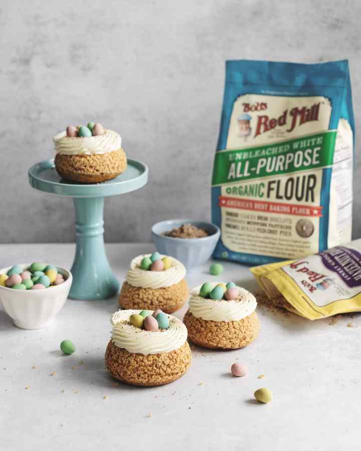 Mini egg cream puffs on cake stand with bag of flour in background
