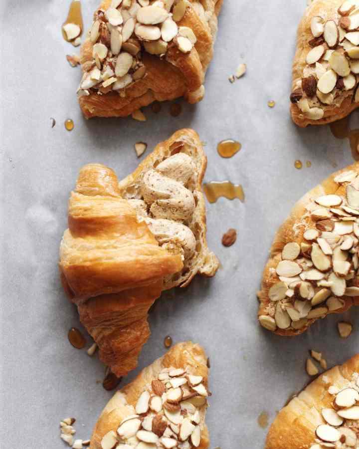 Almond croissants on baking sheet showing the frangipane filling inside