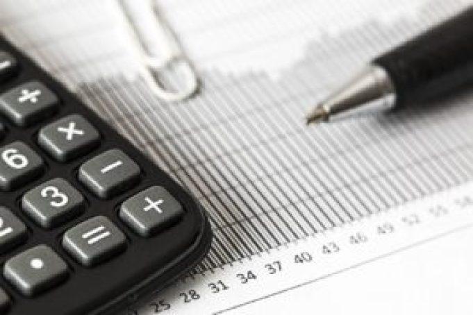 Nessa imagem está um papel com métricas, e três objetos espalhados sob eles: uma calculadora, um clipes branco e uma caneta.