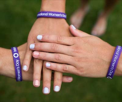 Hands in a circle wearing Internaional Women's Day Bracelets