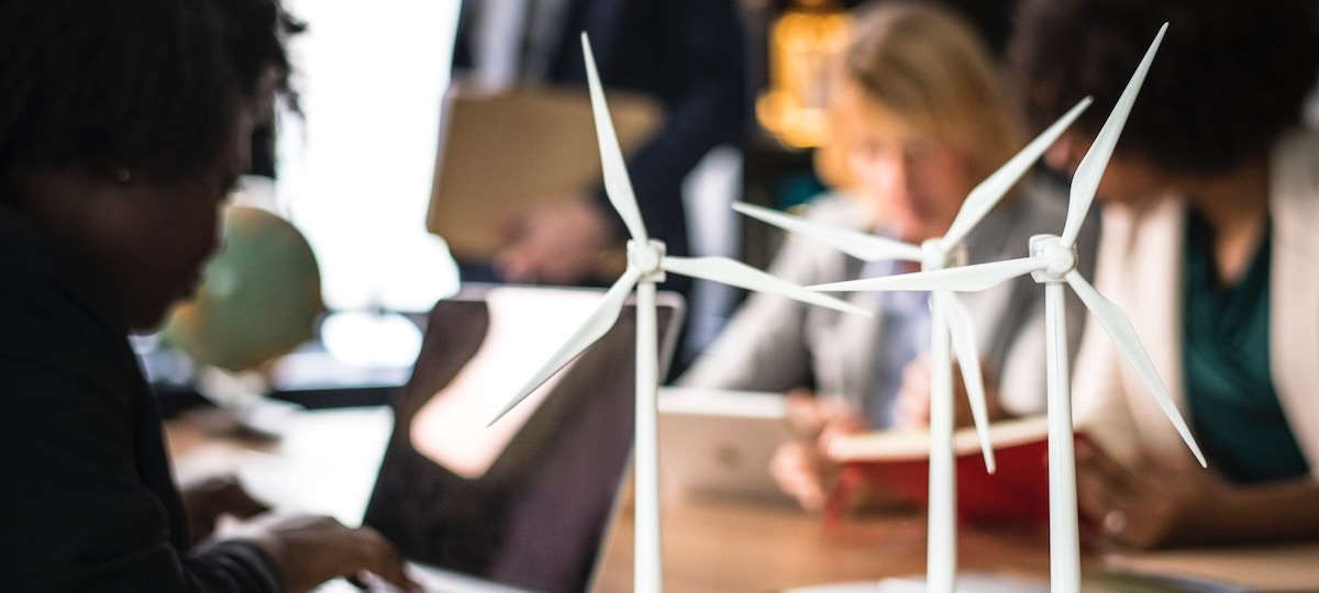women working at desk with wind turbines