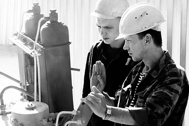 Workers manually inspecting tanks.