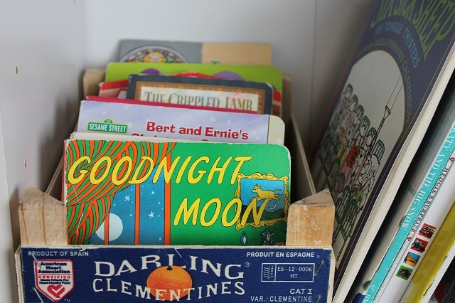 An old clementine box has been repurposed to hold books.