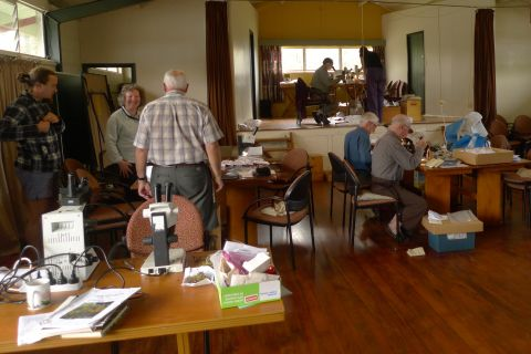 The hall of the camp at Gunns Bush, converted temporarily into a laboratory. Identifying mosses, liverworts, and lichens often requires examination with a microscope. The Te Papa contingent, at right, are hard at work. Some of the Australians, at left, appear to be gossiping. Gunns Bush Camp, Waimate. Photo Leon Perrie. © Te Papa.