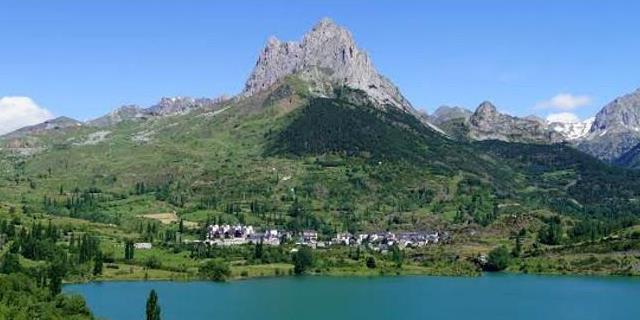 Laguna y paisaje montañoso localizados en el municipio de Sallent Gallego (Huesca).