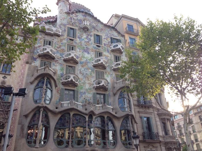 1877年に建設された建物。大繊維業者ジュゼップ・バッリョ・イ・カザノバスの依頼を受け、1904年から1906年にかけて、ガウディが改築を行いました。この改築でガウディは、建物に5階と地下室を加え、玄関広間を広げ、階段や内壁を作り直し、各部屋に曲線的なデザインを持ち込んで、タイルやステンドグラスの装飾を施しました。 この邸宅の造形には様々な説があします。第一に、屋根の一部が丸く盛り上がり、まるでドラゴンの背中のように見えることから、カタルーニャの守護聖人であるサン・ジョルディの竜退治の伝説をなぞっているという解釈です。この解釈によれば塔は聖人の構える槍とされます。カサ・バトリョには、ファサードの石柱が骨を想起させることから「骨の家」というあだ名もありますが、竜退治説によればこの骨もドラゴンの犠牲になったものたちの骨と理解されています。 第二の解釈は屋根をアルルカンの帽子に見立て、ファサードのバルコニーは仮面を、ジュゼップ・マリア・ジュジョールによる様々な色の破砕タイルのモザイクが祭りの紙吹雪を表しているとする謝肉祭説です。 Wikipedia引用。