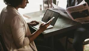 casual dating - sitting at a table with laptop and phone arranging a hook up