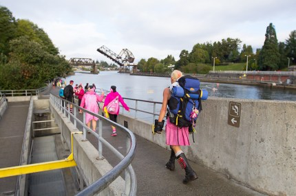 William K in his pink kilt strides through the Ballard locks on his way to the Seattle Center and Closing Ceremony
