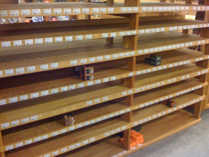 empty ammunition shelves with a sign limiting purchases