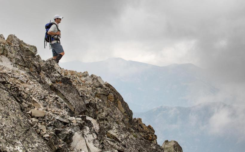 Hiker standing atop a rock outcropping wearing a backpack