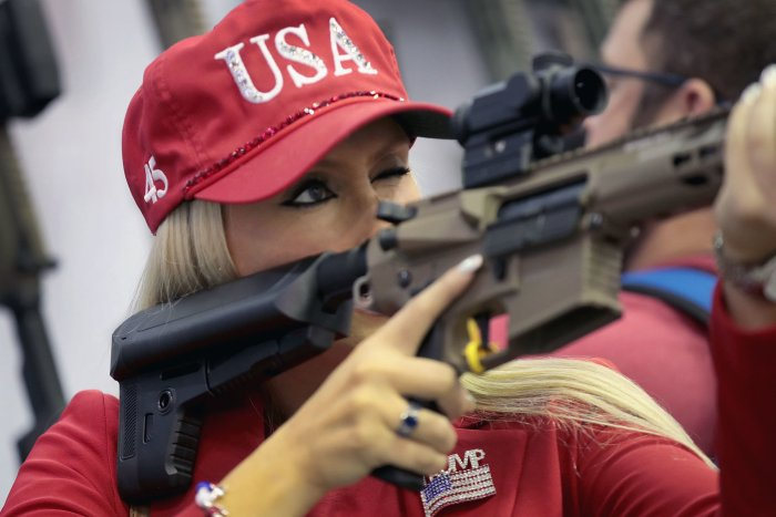 Woman holding an AR-15 wearing a USA hat and Trump polo shirt