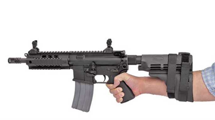 AR pistol with a stabilizing brace strapped to the shooters arm