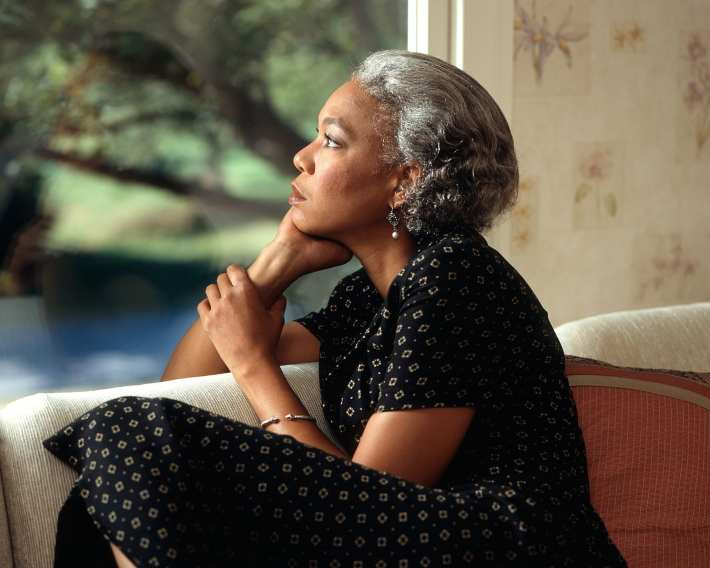 A pensive older black woman looking out a window.