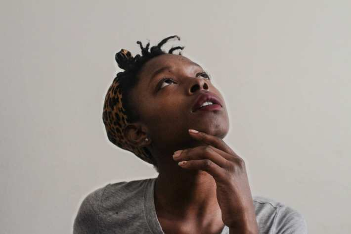 A young dark-skinned woman looking up in a pensive sort of way.