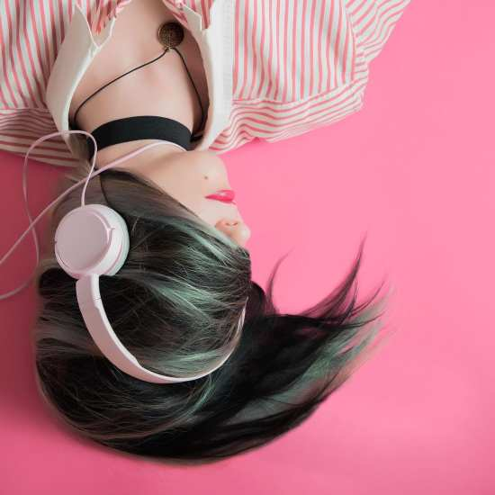 A young woman wearing headphones. Her face is concealed by her hair.