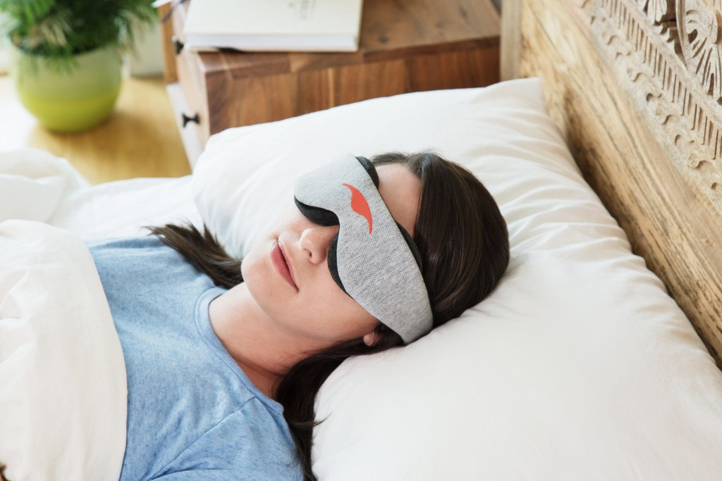 A woman is seen sleeping in bed wearing a grey & black blackout sleep mask from Manta