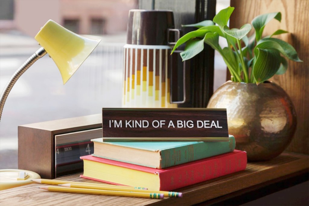 "A snarky nameplate says ""I'm kind of a big deal"" sitting on a pile of books on a desk"