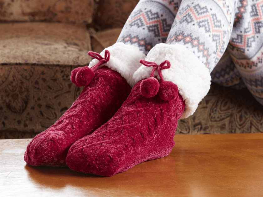 A woman is seen lounging on the couch wearing crimson chenille slipper socks from PUDUS
