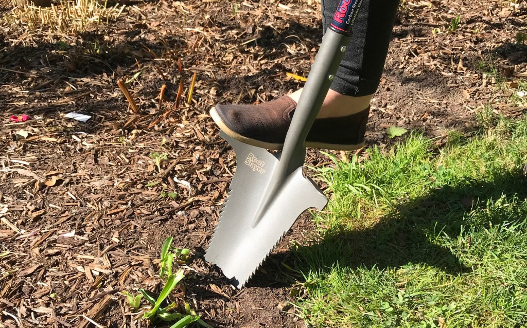 A person is seen applying foot pressure to a Radius Garden root slayer in order to dig up soil