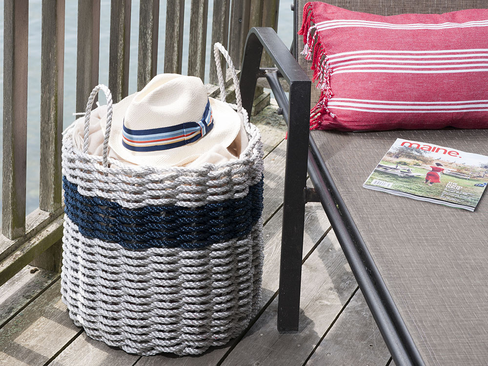 Patio essentials like a sun hat sit stored neatly in a white and blue stripe nautical rope storage big from The Rope Co.