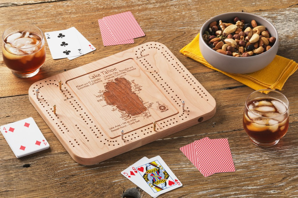 Players enjoy snacks as they play cribbage with a Lake Tahoe laser-engraved custom cribbage board from Lake Art