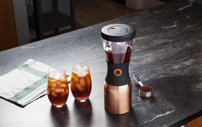 Two glasses of iced coffee sit on a counter next to an Asobu portable cold brew coffee maker