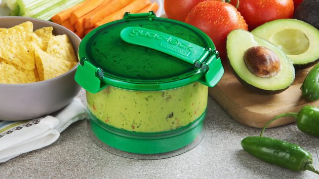 Fresh guacamole, chips & veggies sit on a counter, the guacamole covered by Guac Lock
