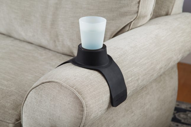 A cup sits in a black CouchCoaster weighted drink holder on a beige couch