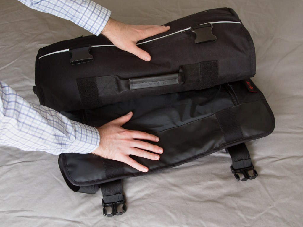 A man rolls up his suit into Henty's roll up garment backpack
