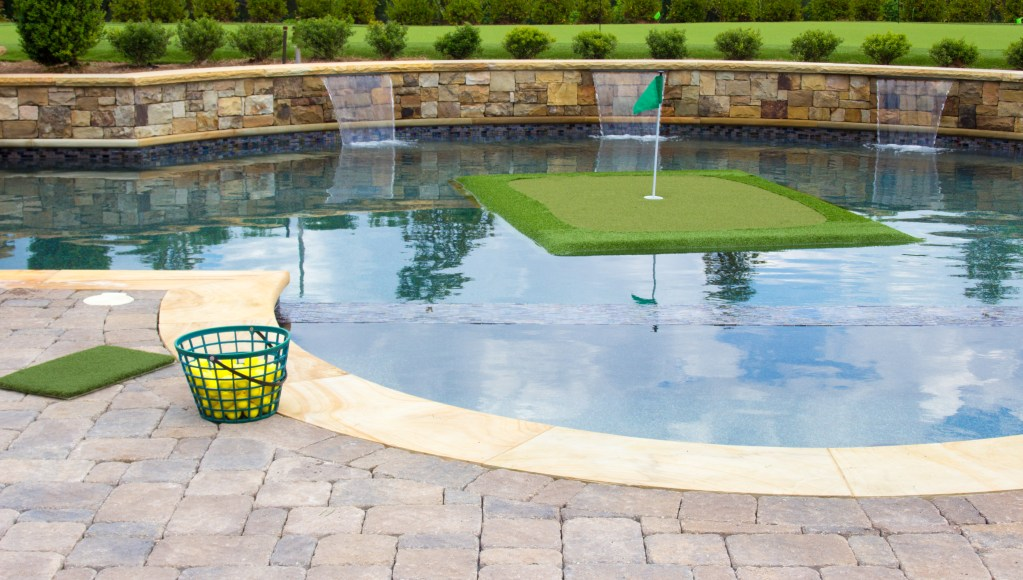 A floating golf turf from Floating Golf Greens can be seen in a pool, with golf balls on the patio.