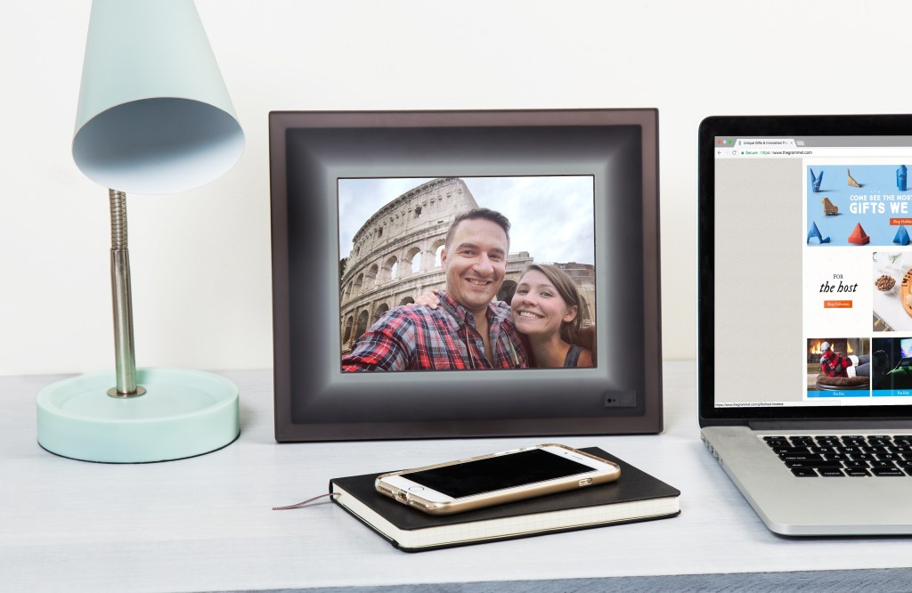 A photo of a couple posing in front of the Colosseum in Rome displays on a smart connected picture frame from Aura