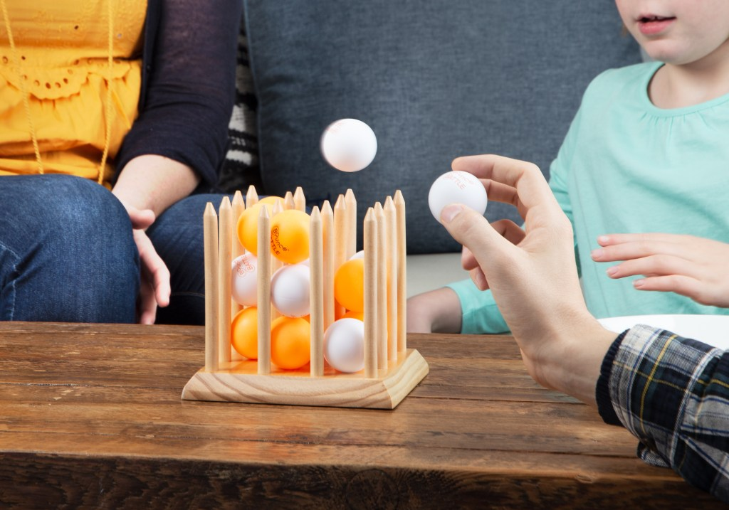 A family is seen playing Bounce Battle around a coffee table