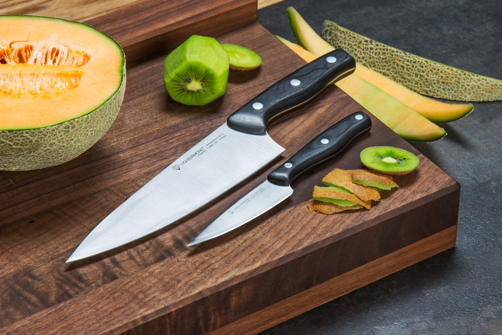 professional-grade amorphous kitchen knives from LiquidDiamond Knives sit on a cutting board with cantaloupe & kiwi