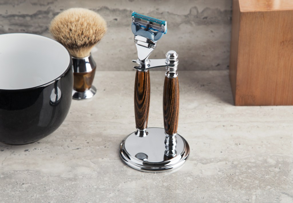 A beautifully handcrafted Tiger Wood razor handle and stand from Imperium Shaving sits on a bathroom counter