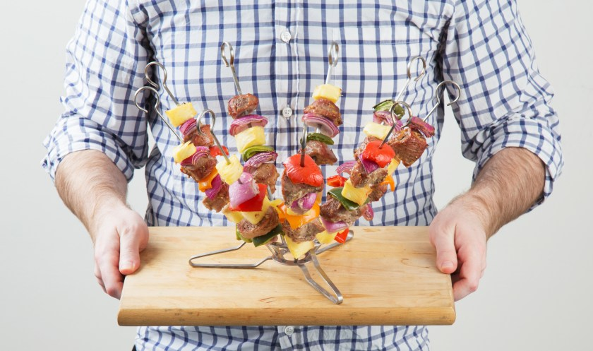 A man holds a cutting board with O-Yaki's standing skewer cooking system loaded up with fresh meats & veggies ready to be grilled