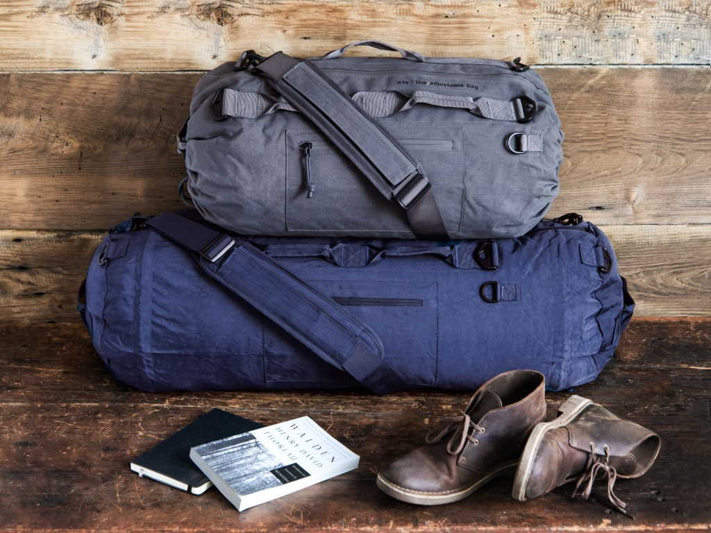 Navy and gray PIORAMA expandable duffel bags are seen next to books and a pair of men's shoes
