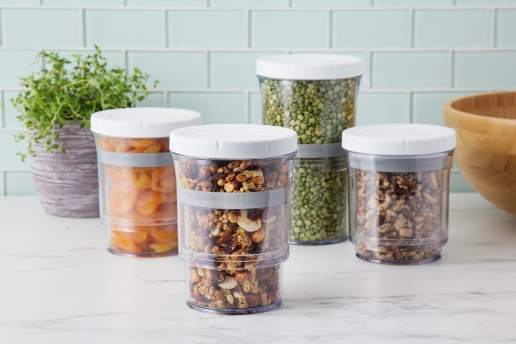 Fruits, nuts and grains sit on a countertop stored in adjustable storage containers from Botto