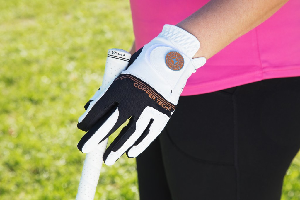 A woman grips her golf club with a white & black Copper Tech copper-infused golf glove