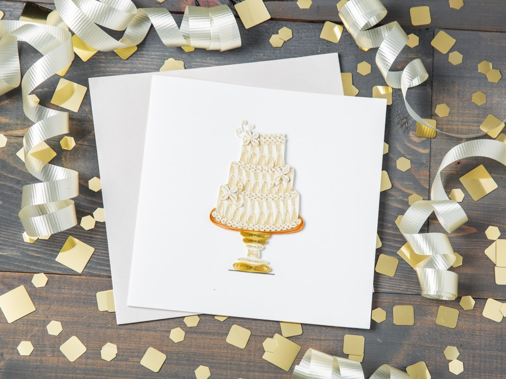 A wedding cake quilled card from Quilling Cards sits on a table amongst gold confetti
