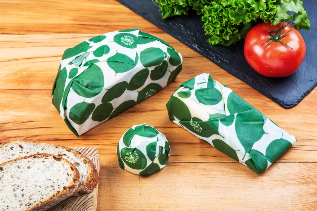 Several food items sit on a counter wrapped in green and white beeeswax food wraps from  Z Wraps