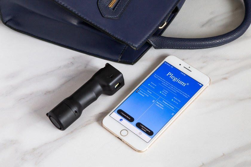 A black 5-in-1 pepper spray from Plegium sits next to phone with the Plegium safety app pulled up