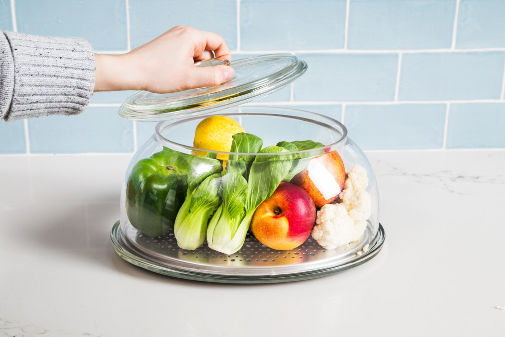A woman opens the lid of VeggiDome's glass tabletop product saver, filled with fresh fruits and veggies