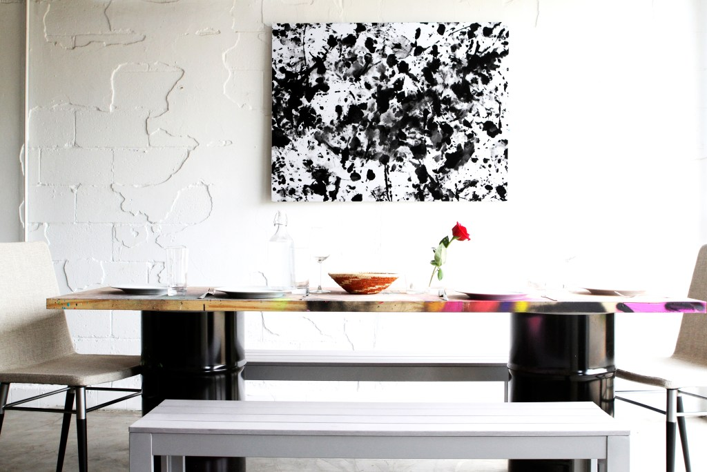 A black & white abstract passion painting from LOVE IS ART hangs in a dining room