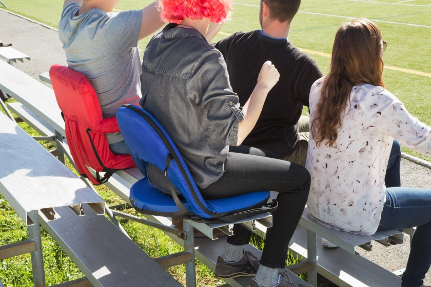 Fans sit comfortably in the stands with red and blue Oniva Picnic Time reclining outdoor seats