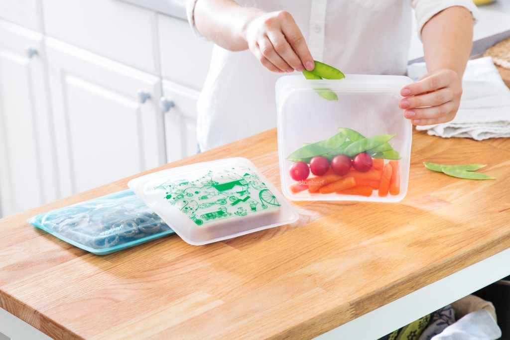 A woman fills reusable silicone storage bags from stasher with fresh carrots, tomatoes & snow peas